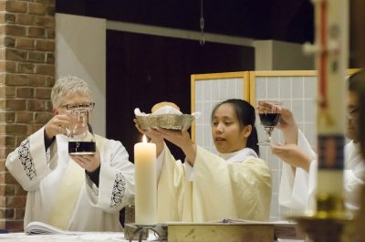 Three people preparing communion at altar.