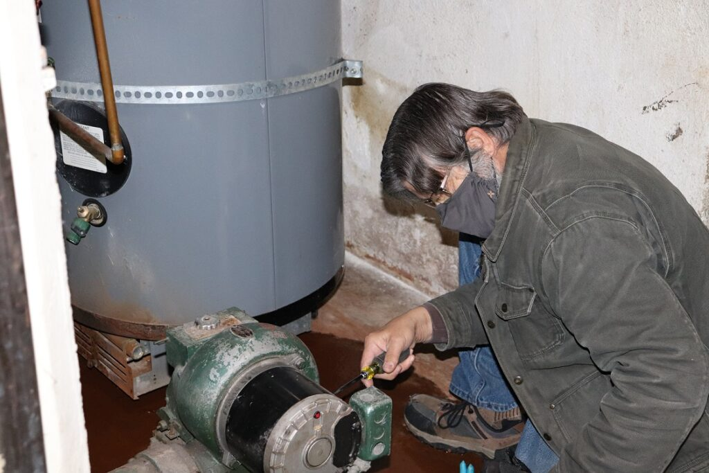 """Steve Sibbitt restarts the Gibbs Hall boiler after an unexpected shutdown. """"I'm not afraid to touch anything or take anything apart,"""" he said."""